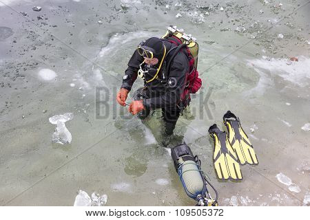 Diver Preparing For The Ice-diving Under The Frozen Surface Of Lake