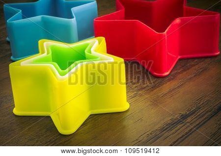 Rainbow Plastic Stars on Wooden Background