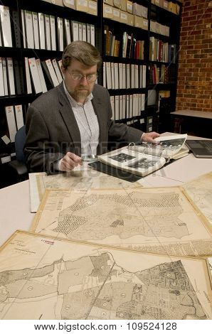 Researcher In Archive, Searching Through Maps And Photographs.