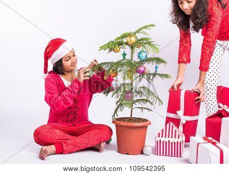 indian girls decorating christmas tree, christmas tree decoration, indian girl preparing for christm