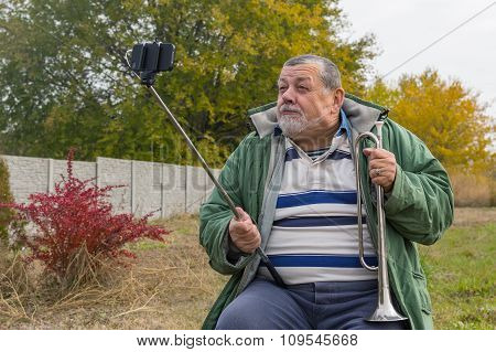 Ridiculous senior man making faces while doing selfie outdoor