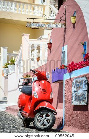 Red motor scooter as a part of decoration at color street of Thira town