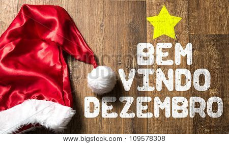 Welcome December (in Portuguese) written on wooden with Santa Hat
