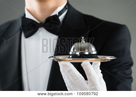 Midsection of waiter holding service bell in plate against gray background poster