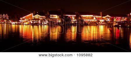 Christmas Lights Of Houses Reflecting On Lake