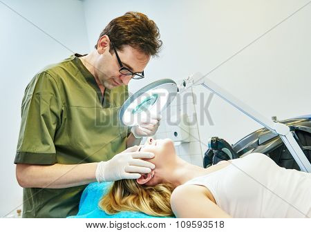 Male doctor cosmetologist examining young woman skin with loupe before the cosmetology procedure