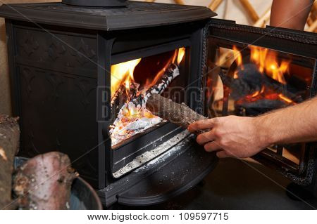 Man Putting Log Onto Wood Burning Stove