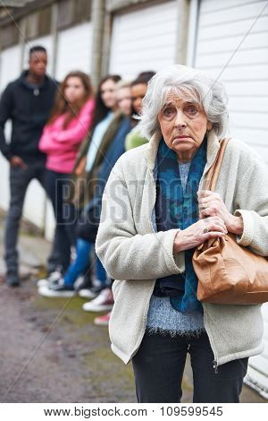 Senior Woman Feeling Intimidated By Group Of Young People