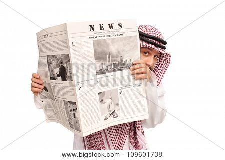 Sacred young Arab hiding behind a newspaper and looking at the camera isolated on white background