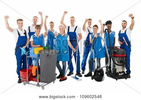 Happy Janitors With Arms Raised Holding Cleaning Equipment