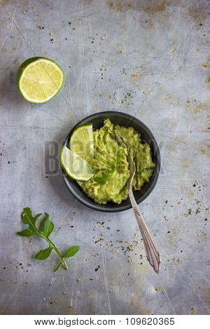Guacamole Dip And Lime On Rustic  Background