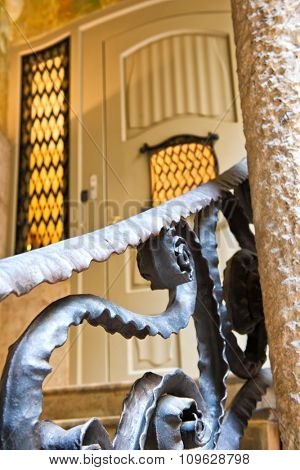 BARCELONA, SPAIN - MAY 01. Close Up Detail of Iron Railing Leading Up Staircase to Closed Door in Case Mila, Designed by Gaudi and a Popular Tourist Destination in Barcelona, Spain. May 01, 2015
