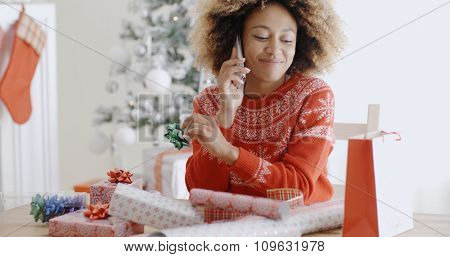 Young African woman chatting and laughing on a mobile phone as she sits at a table in the living room wrapping Christmas gifts
