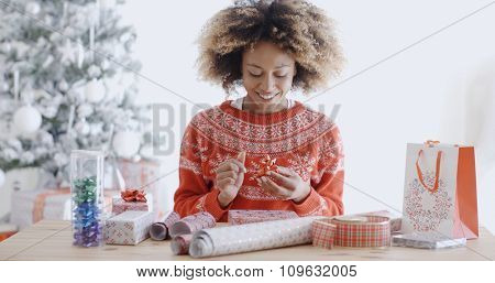 Attractive young African woman wrapping Christmas gifts as she sits in front of the decorated tree in her living room