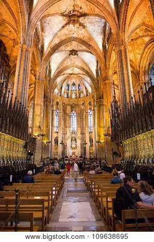 BARCELONA, SPAIN - MAY 02: Interior of Barcelona Cathedral with View Down Central Aisle Between Pews Filled with People Looking Toward Altar, Barcelona, Spain. May 02, 2015