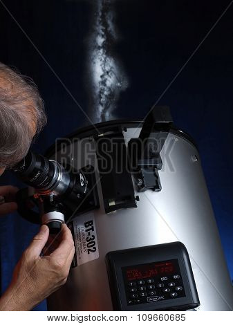 Amateur astronomer with a telescope looki