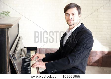 Close up portrait of handsome musician in black suit plays piano in the class
