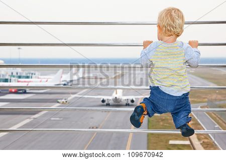 Baby Boy In Airport Transit Hall Looking At Airplane