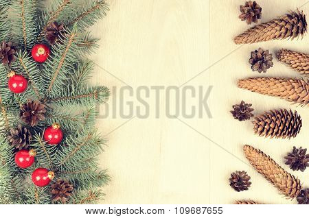 Branches Of Blue Spruce, Red Balls And Fir Cones On A Wooden Background
