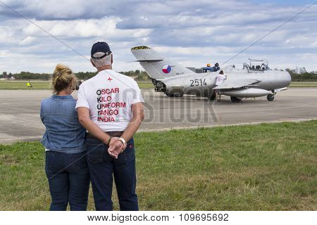 HRADEC KRALOVE CZECH REPUBLIC - SEPTEMBER 5: Former owner collector Tom Smith looking at jet fighter aircraft Mikoyan-Gurevich MiG-15 standing on runway on September 5 2015 in Hradec Kralove Czech republic. poster