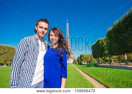 Young happy couple on the Champ de Mars in Paris background the Eiffel Tower