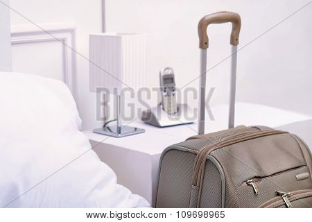 Suitcase standing near the bed table.