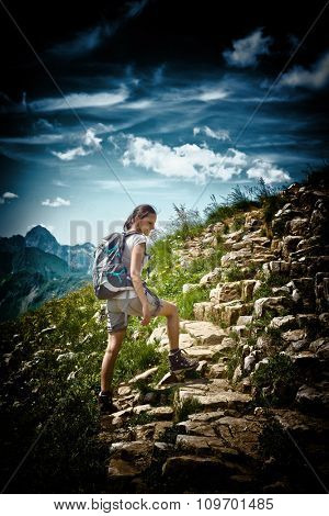 Vignette Style Image of Young Woman Wearing Backpack Hiking on Rocky Mountainside Trail with View of Mountain Vista and Blue Sky with Clouds