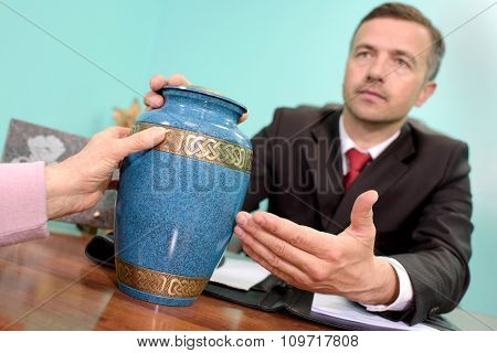 funeral director showing urn
