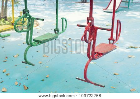 Empty hourse swings on summer kids playground poster