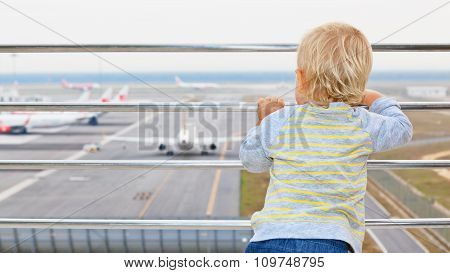 Young Passenger Looks At The Plane In Airport