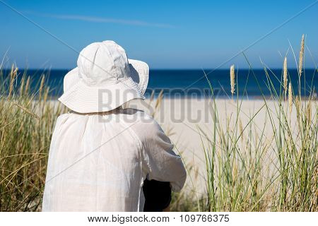 Woman Sitting On Sand Dune And Looking At Sea