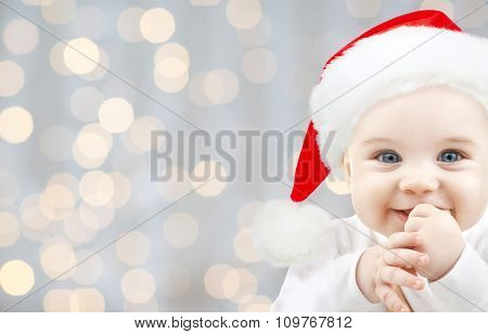 christmas, babyhood, childhood and people concept - happy baby in santa hat over holidays lights background poster