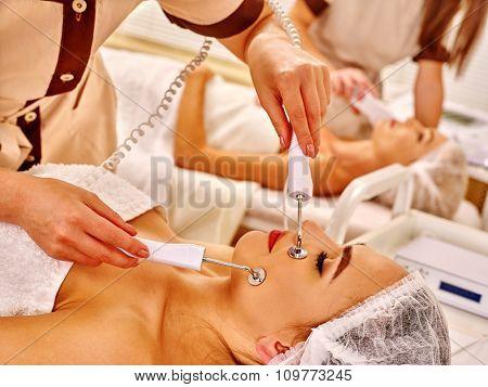 Group young women receiving electric facial massage at beauty salon. Close up.