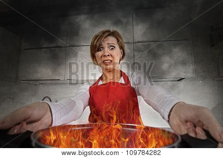 young inexperienced home cook woman in panic with apron holding pot burning in flames with stress and panic face expression in fire in the kitchen and amateur newbie rookie ad messy cooking concept poster