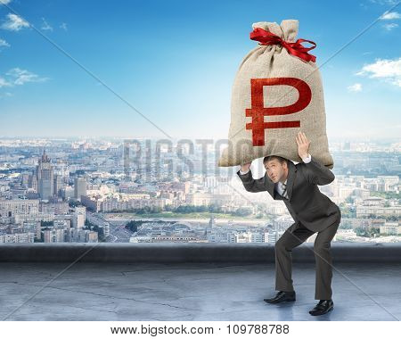 Businessman holding big moneybag with ruble sign