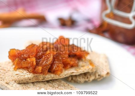 Canapes with homemade onion chutney with ginger and red pepper on a white plate. Selective focus on a chutney.