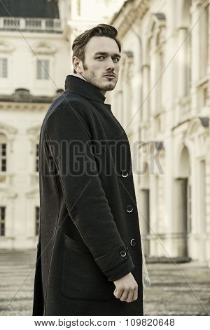 Handsome trendy man outdoor by historic building in Europe