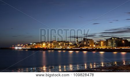 City on the bank of ocean bay and light trails at night. Salthill Galway