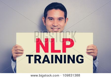 NLP TRAINING message on white cardboard held by smiling man vintage tone