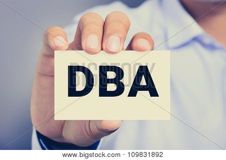 Dba Letters (or Doctor Of Business Administration) On The Card Shown By A Man