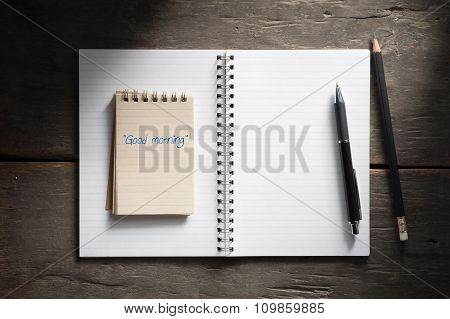 """Good morning"" is written on small notepad with pen and pencil on rustic wood background in morning time with low key scene."