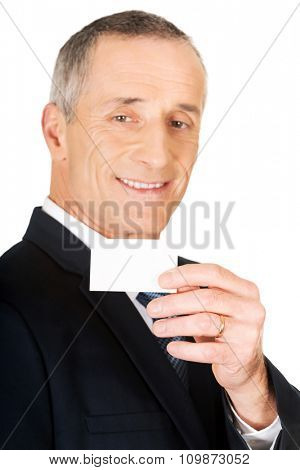 Mature businessman showing a blank identity name card.