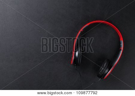 Headphones on black leather desk table. Music concept. Top view with copy space