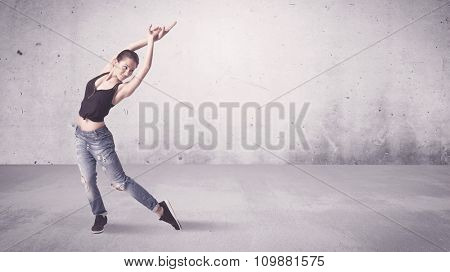 A beautiful young hip hop dancer dancing contemporary urban street dance in empty clear grey wall background concept. poster