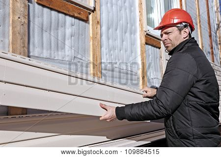A Worker Installs Panels Beige Siding On The Facade