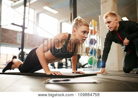 Trainer Helping Woman Do Push Ups