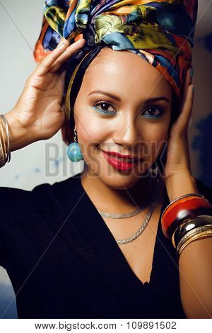 beauty bright african american woman with creative make up, shawl on head like cubian closeup
