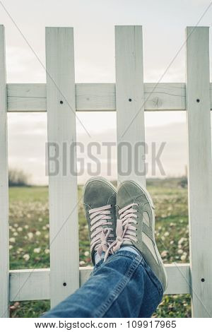 escape from city, woman legs in jeans and sneakers lean on wooden fence in countryside, relaxing, focus on sneakers