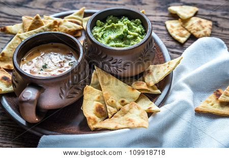 Bowls Of Guacamole And Queso With Tortilla Chips