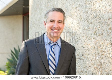 Mature happy smiling business man outside his office